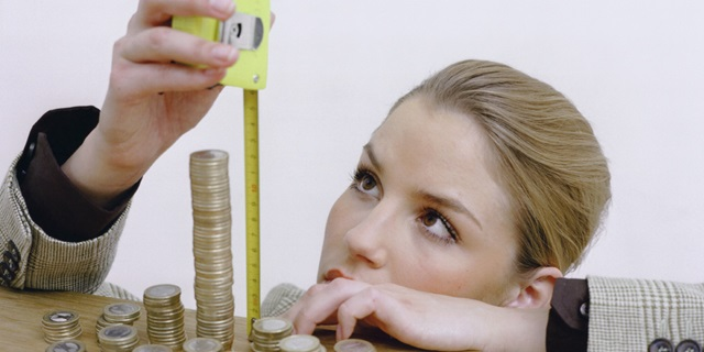 Business lady measuring tower of coins with a measuring tape