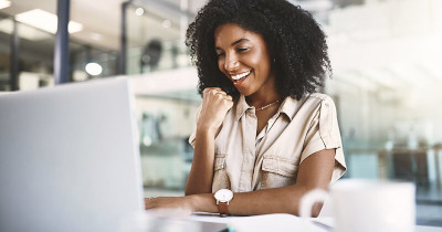 Woman smiling looking at her laptop