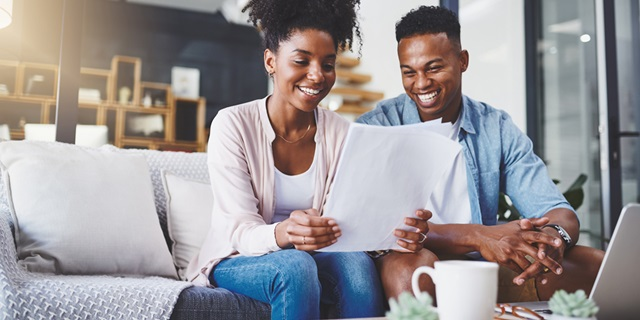 A young couple sitting on the couch smiling looking at paperwork
